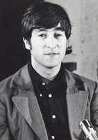 Black and white photograph of John Lennon, wearing a black shirt and gray jacket, donning a somewhat wry smile.
