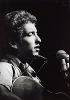 Black and white photograph of Bob Dylan playing a guitar in front of a microphone.