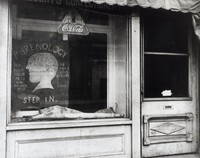 "This black and white photograph represents a storefront door and window, with a small segment of the shop's awning pictured in the upper right corner. Through the storefront window, two signs can be read and a third can be seen laying crumpled on a ledge. The first legible sign is hung at the top of the window, advertising Coca-Cola. The second reads: ""Phrenology / She reads your head like an open book / She speaks several languages / Step in,"" with an image of head subdivided and numbered at the center. There is also illegible text at the top of the image, cut off by the awning, and ""AVAL BRIGADE"" reflected from across the street in the shop window."