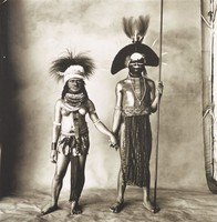 This black and white photograph is printed adhered to an aluminum plate that is visible at the top of the sheet. There are six holes in the aluminum. In the image, two central figures stand in front of a draped studio backdrop, holding hands. At the right of the composition, the edge of the backdrop can be seen next to a tent pole. The female figure wears a headdress, a mask, and necklaces. The top of her body is nude, but she wears a belt holding drapery on her body. The male figure also wears a headdress and a mask. He holds a staff, and his costume covers a portion of his chest and attaches to a belt covering him with drapery.