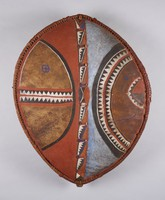Hide shield attached by leather strips to oval wooden frame; vertical wooden handle on back; patterns in blue, white, black, ochre, red pigments.