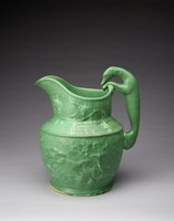 A press-molded circular pitcher with matte green galze, with a broad spout and tall neck decorated in relief with a grapevine motif. The handle is in the form of a greyhound, which appears to be climbing into the jug. The body is decorated in relief with hunting scenes: hounds attacking a stag on one side and mastiffs attacking a boar on the other.