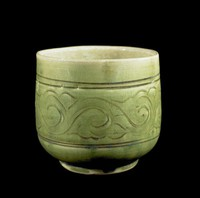 Beaker with incised and combed scrolling decoration, brown wash in base.