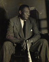 In this black and white photograph, a smiling African American man wearing a suit and tie sits, holding the comics section of a newspaper between his knees. There is a long diagonal crease that moves into the image from the upper left corner, and there is intermittent pink-red spotting on the left half of the image.