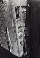 This black and white photograph shows a partial view of an airshaft of a brick building. From its vantage point, the viewer looks down on three stories of windows, some with curtains. The view of the airshaft is cut diagonally with shadow, which runs from the top to the bottom of the photograph. A line—possibly a clothesline—runs through the airshaft.