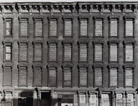 """This black and white photograph represents a cropped view of a building, which fills the entire picture. Part of its first story is visible at the bottom of the photograph, the top half of the door surrounds for the building's entrances. Some of the first floor windows and doors are covered with signs, including two reading """"LOEW'S ORPHEUM"""" across the top. There are three additional stories, all with boarded up windows. At the top of the image is the building's dentil cornice."""