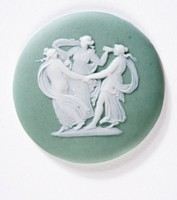 Round green jasper medallion with white relief of three women holding hands and dancing