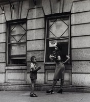"""This black and white photograph shows an African American woman and an African American boy facing each other on a street or sidewalk. The boy wears overall shorts and a white t-shirt and raises his arms in front of his chest. The woman wears high heels, a skirt, and a black short sleeved shirt and has one arm on her hip with the other carrying something. There are two windows behind the group, and in the window behind the woman, a posted sign reads """"FURNISHED / ROOM."""" From within the window—beneath the sign and behind the woman—another figure's face is seen."""