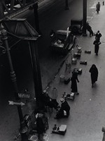 "In this black and white photograph, a street and sidewalk are seen from above. Two vehicles are parked on the street, and a number of figures occupy the sidewalk. Some of the figures are shoe shiners, with shoe shining stands and chairs near the curb, and others are passersby. One man is seated, having his shoes shined by another man. A metal girder is seen in the foreground of the image, holding up what could be a train track next to the post for a street light. On the lower half of the post, two signs hang. One includes an image of an arrow pointing right and reads ""TERMINAL."""