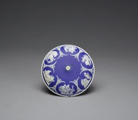 """Cover to a dish or bowl of white jasper with dark blue jasper dip and white relief decoration, the cover domed and missing its finial, around the sides are six small relief scenes between decorative elements of leaves and anthemion motifs, the scenes include """"The Muses Watering Pegasus,"""" """"Bellerophon Watering Pegasus,"""" """"Priam begging Achilles for the Body of Hector,"""" """"Sacrifice to Aesculapius,"""" a group with a cage, and """"Aurora."""""""