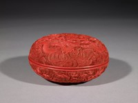 A round covered box decorated with a carved dragon on the top.