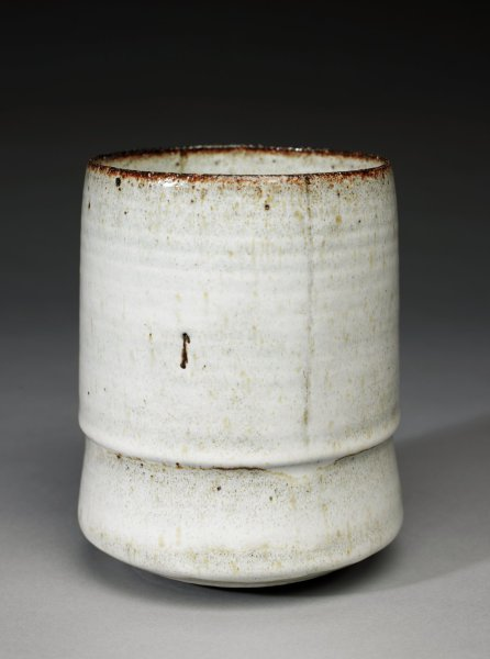 Tall vase of red earthenware covered inside and out with an opaque white glaze that runs thick and thin over the piece revealing the structure of the vase below, the rim left glaze-free, with flecks and speckles throughout.