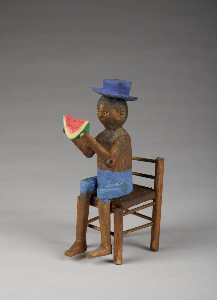 Young man wearing hat and sitting in chair, holding a slice of watermelon.
