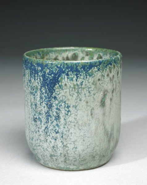 Tall bowl, or beaker, of rough beige stoneware, covered with a thick, opaque bluish green with gray mottled and drippy glaze in irregular shades ranging from light to dark.