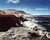 This color photograph shows waves rolling in from the open ocean at the right of the image and crashing over rocks beneath a blue, lightly clouded sky. These rocks rise into a rocky, hilly coastline at the left of the image.