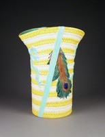 """Majolica """"Kate Greenaway"""" umbrella stand in the form of a yellow and cream straw bonnet with turquoise ribbon tied in a bow on either side and a peacock feather, the interior and bottom glazed turquoise."""