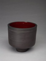 Vase with a bucket form and a tapered base. The exterior is decorated with dimensional bands throughout the form. The rim of the vase has a slightly pronounced lip. The interior is glazed an iron/dark red, which is interrupted at the base where the form begins to taper in.