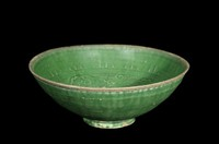 Dish with molded floral scrolls between squared-spiral bands, chrysanthemum in well, lead-green glaze.
