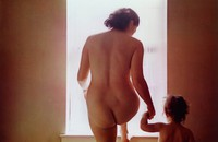 This color photograph shows an adult nude female figure standing in front of a window in a nondescript room with her right foot on the window sill. Her right hand holds the left hand of a child, who also appears to be nude.