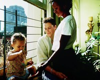 A white woman and black woman with a child in front of a window