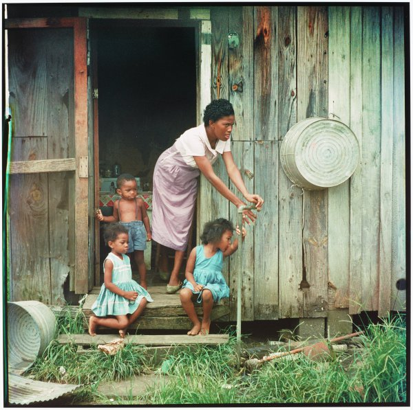 A black woman, surrounded by three children, stands in the doorway of a weathered wooden house. She is reaching to use a water spicket just outside.