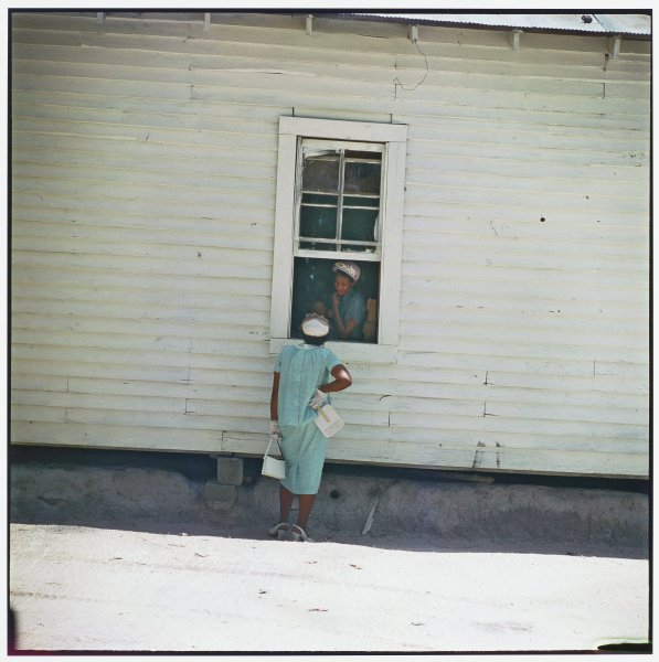 A woman in church clothes stands in shadow at the window of a white building, her back to the camera. She is speaking to a woman just inside.