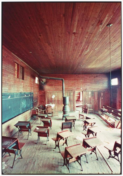 A number of small desks, a long blackboard, and a pot-bellied iron stove fill a large open classroom. The walls, ceiling and floors all appear to be surfaced in the same wooden boards.