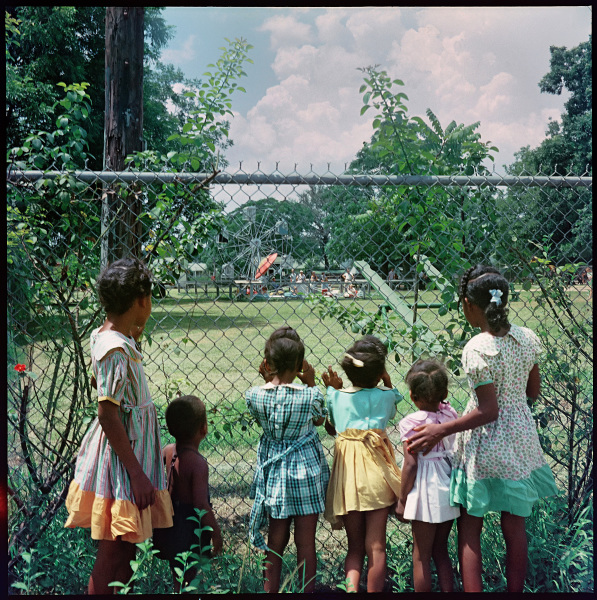 The camera views over the shoulders of a group of black children who stand outside a chain link fence peering at a Ferris wheel and other activities at the park within.