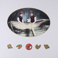 The predominant image, a photolithograph of two girls posed in a rowboat, set within a gold-lined oval, is centered within the top two-thirds of the sheet. Running horizontally along the lower half of the sheet, four inches from the bottom, are five hand-drawn fortune cookies. The center cookie is partially obscured by a red negation sign.