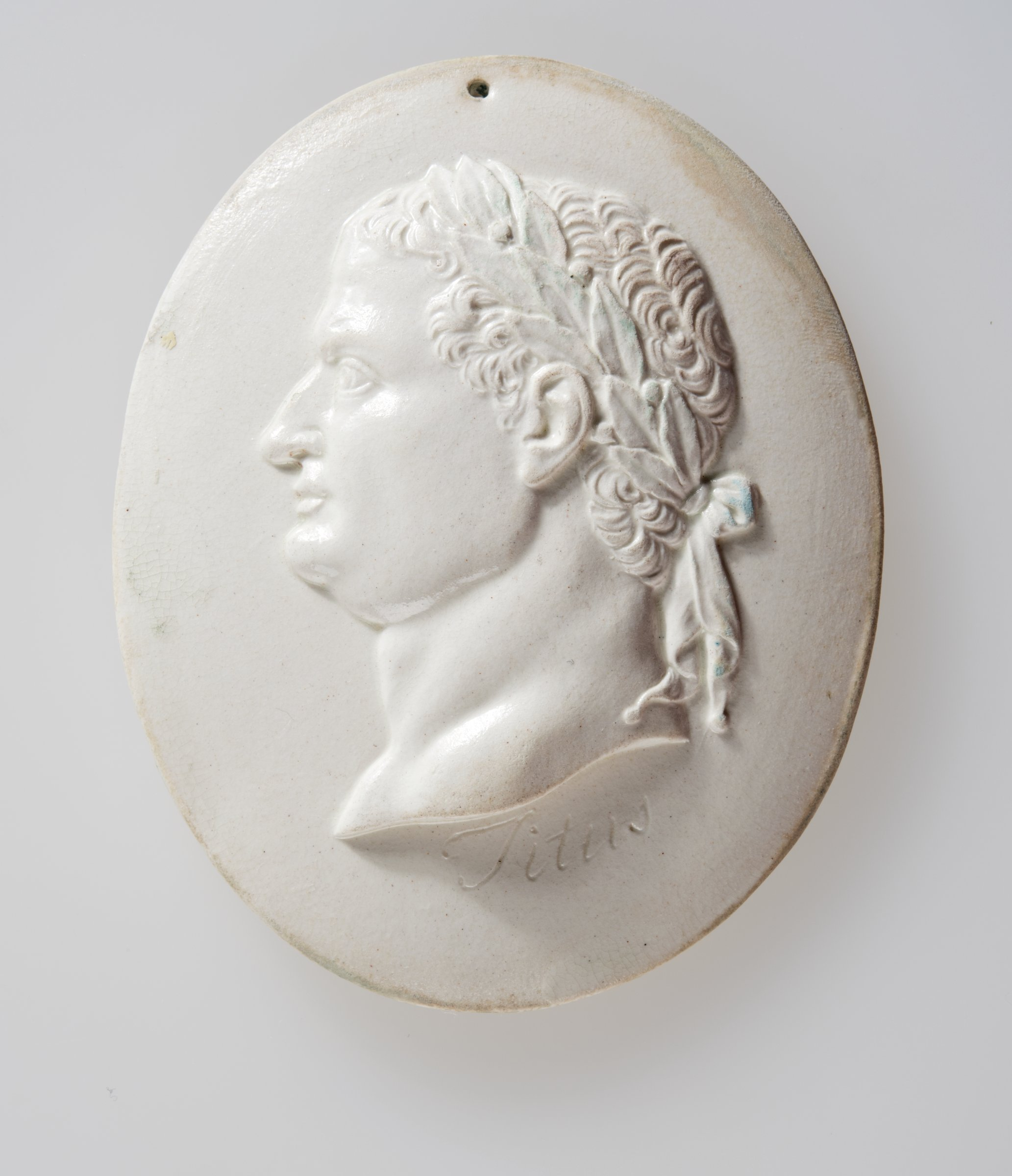Oval, creamware portrait medallion of the Roman Emperor Titus wearing laurel leaf crown to left, the name Titus inscribed below the truncation.