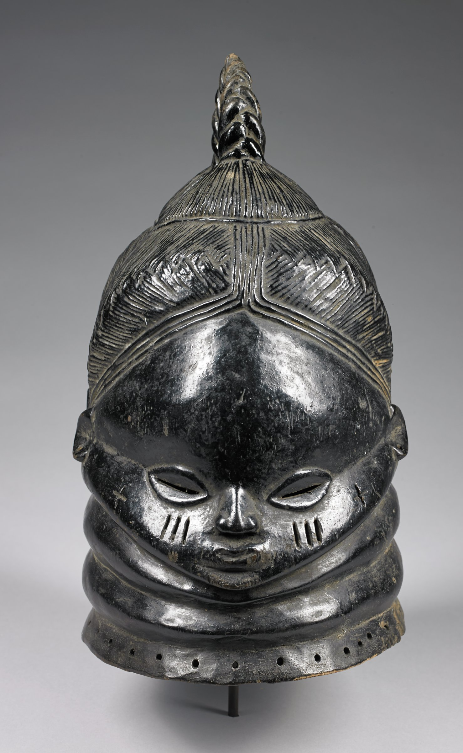 """Helmet mask with glossy, black surface; coiffure of fine plaits close to the skull leading to thick braid rising from top of head. Prominent, domed forehead, slitted """"cowrie shell"""" shaped eyes, small mouth, nose, and ears; three vertical scarification marks on each cheek. Two bulging rings around neck; base of mask pierced with multiple holes for attachment of fiber costume.Function: Worn by women of the Sande Society during initiation of girls into the society, and on other occasions; morphology of the mask reflects Mende ideals of feminine beauty and power."""