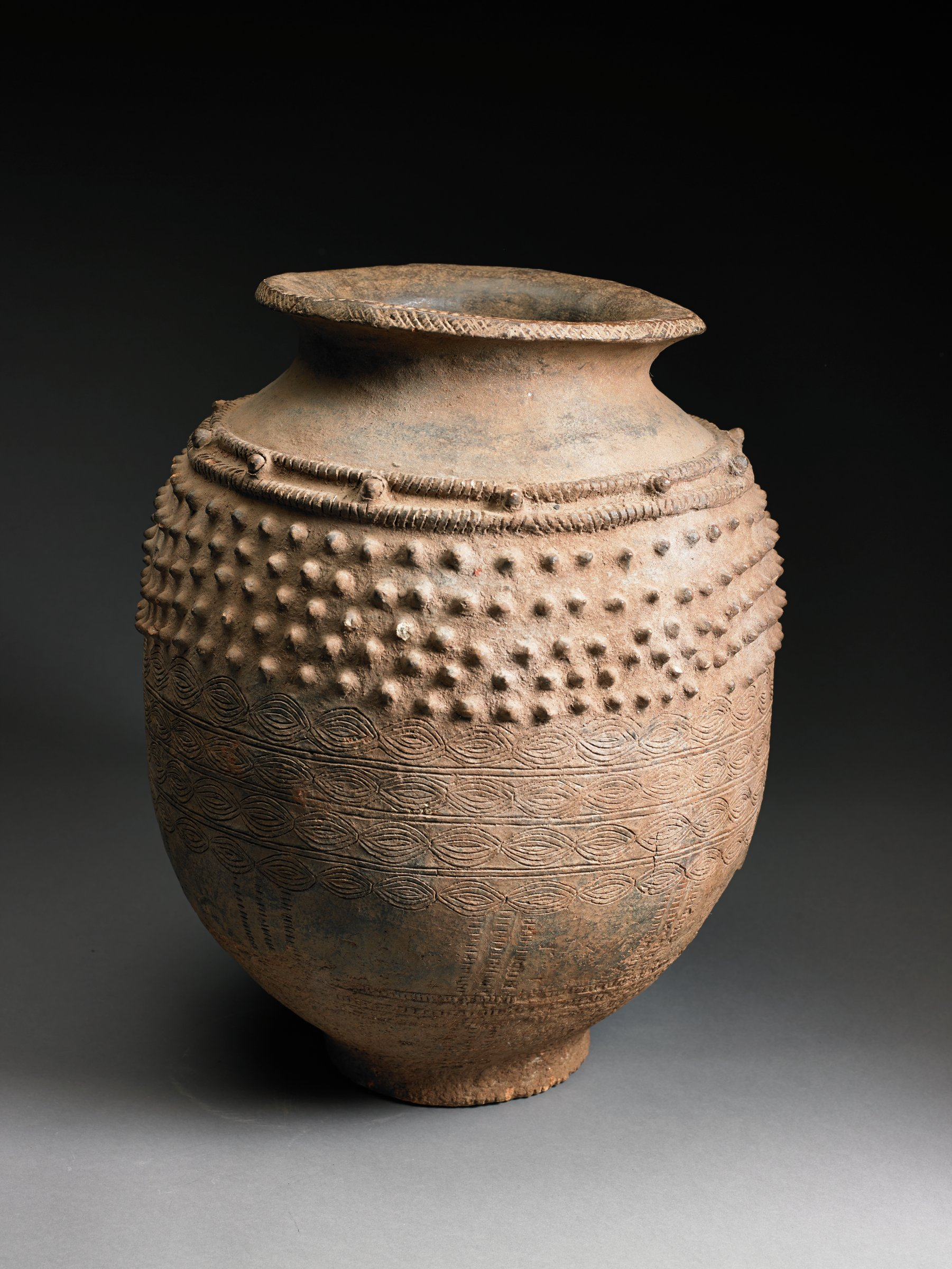 Oval-shaped vessel tapers to narrow, flat base. Narrow curved neck has flaring rim; shoulder has five rows of raised bumps. Body of vessel has four rows of repeating incised garlands.