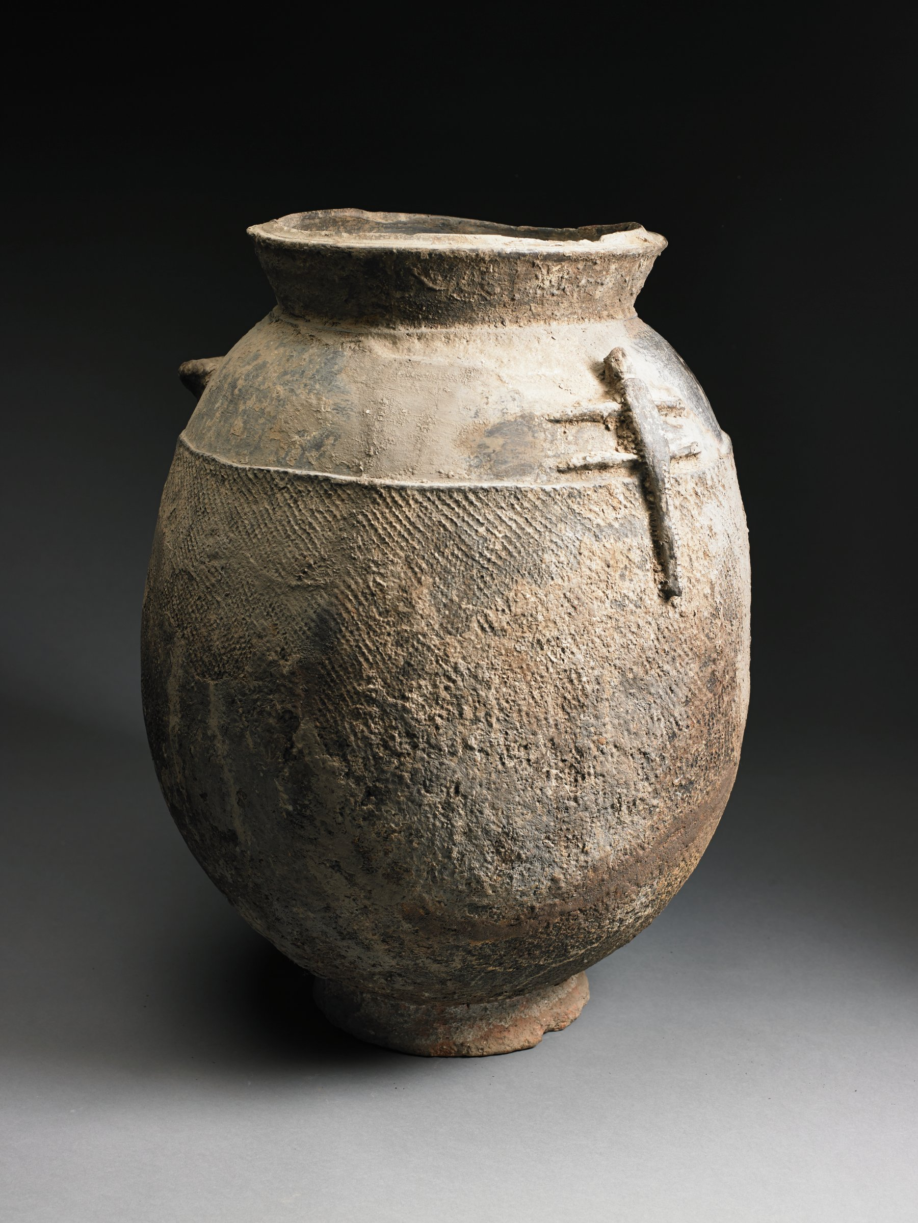 Brown ovoid jar with single ear-shaped handle has short, narrow vertical foot and slightly flared lip. Body of jar has texture from impressed cord and modeled lizard form.
