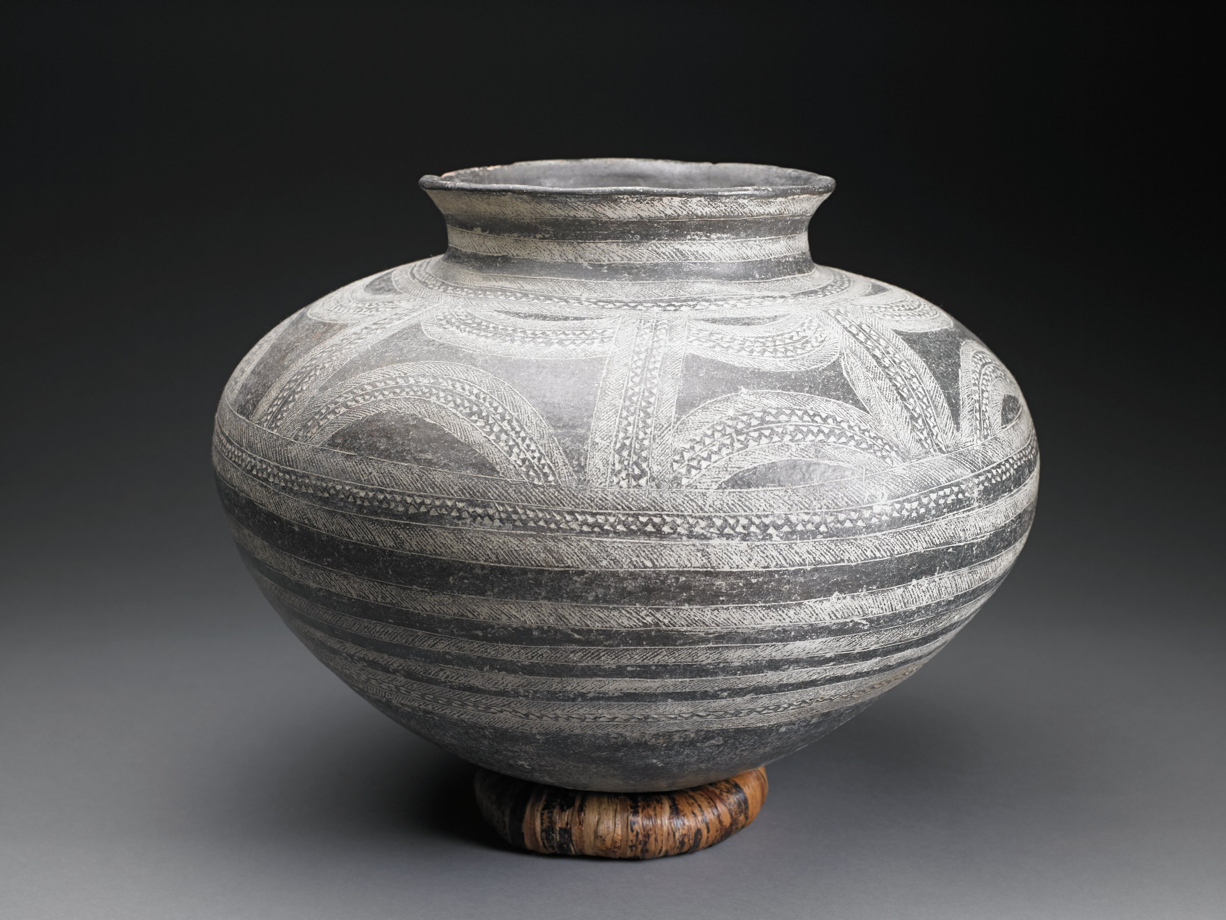 Wide, dark brown vessel with narrow mouth has short, flared lip and narrow base. Incised decorative patterns filled with white pigment include parallel bands around body of vessel, and opposing half circles on shoulder.
