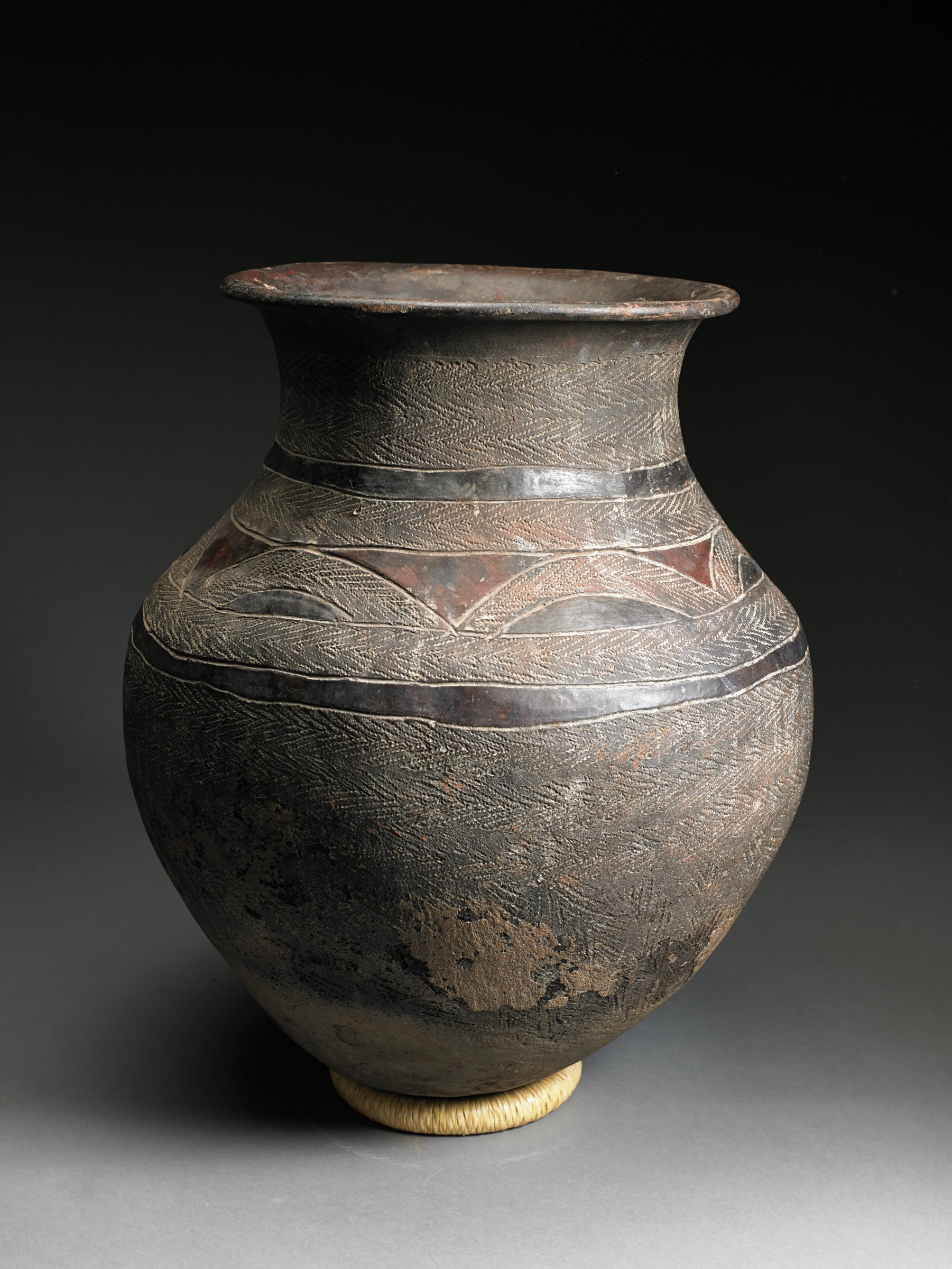 Dark brown vessel has round body and curves inward at neck topped by flaring rim. Surface has overall matte texture from roulette; two narrow glossy bands define shoulder, which has glossy triangles and half-ovals.
