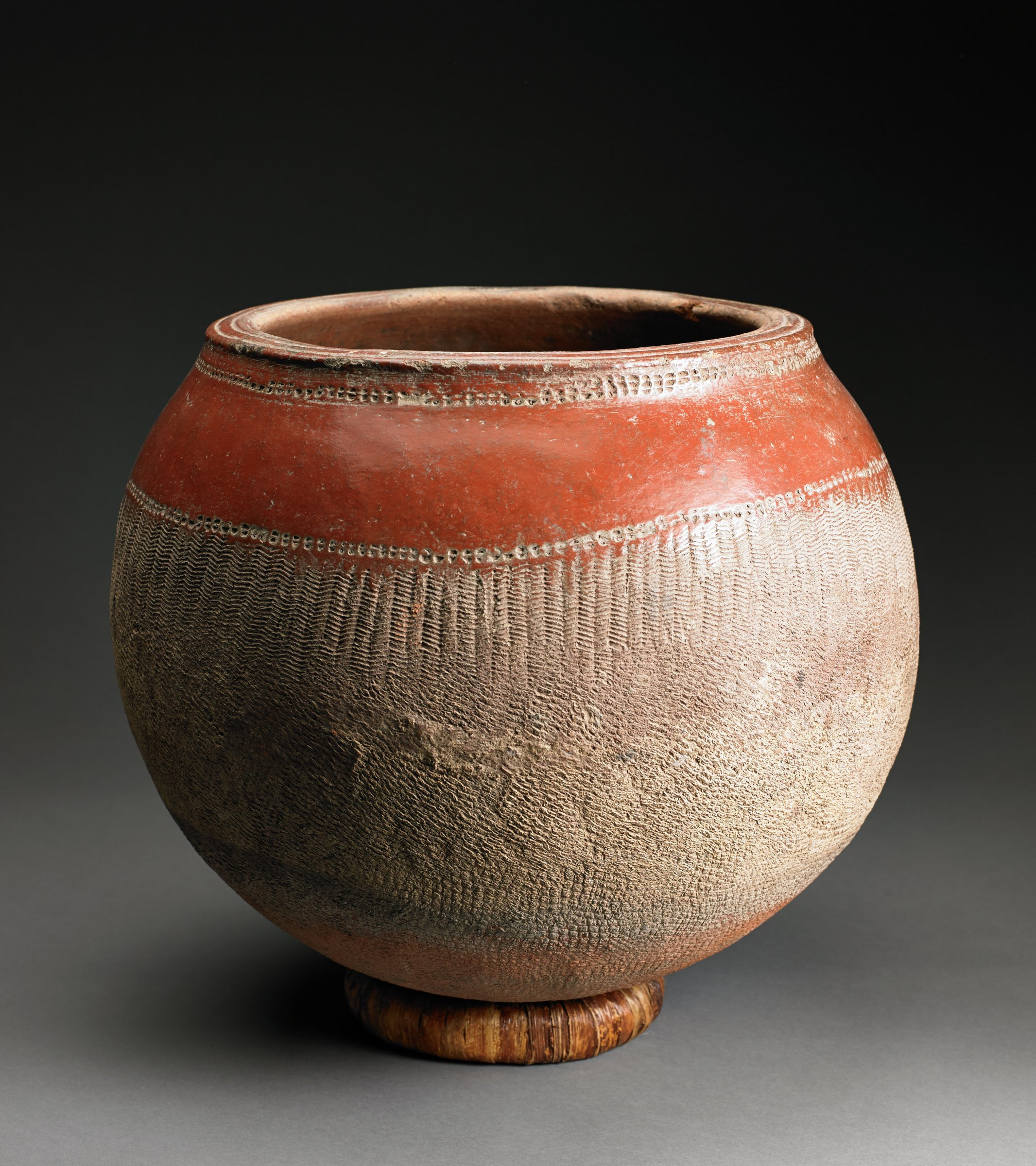 Round, red-orange vessel has wide mouth; shoulder has glossy surface and bottom two-thirds has matte, buff-colored surface with faint roulette texture.