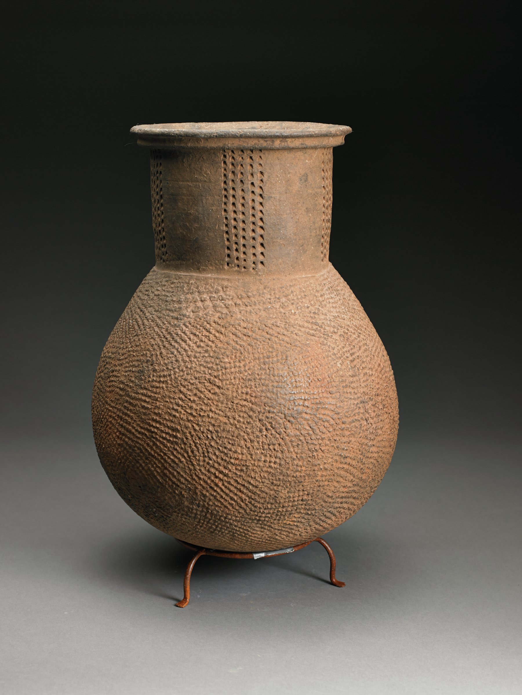 Light-brown, round vessel has tall, wide cylindrical neck; body has overall roulette pattern and neck has columns of impressed marks.