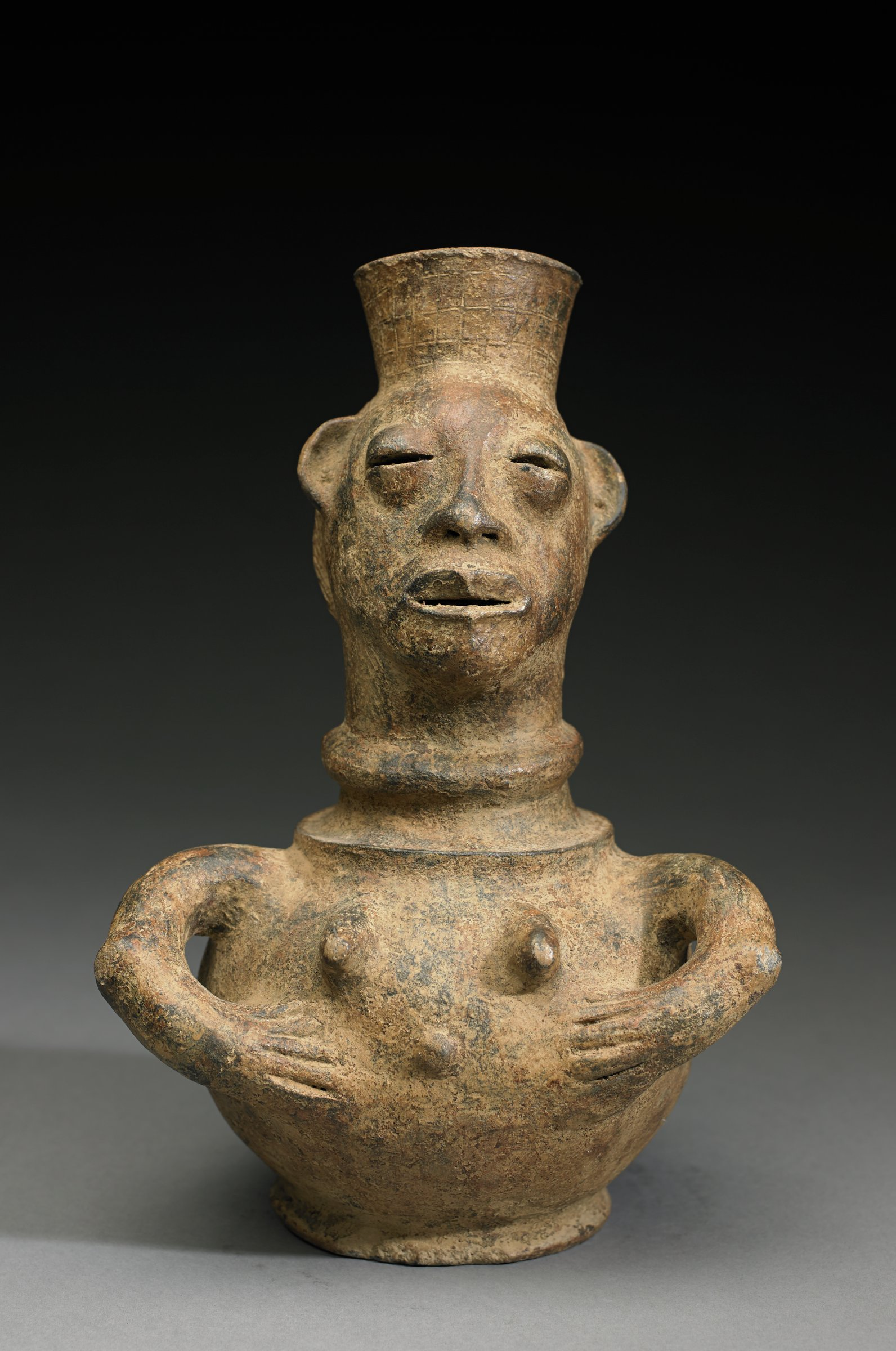 Figurative vessel has curved arms with hands resting on abdomen just below breasts; head has modeled features and plaited hair. Slightly flared opening to vessel rises from top of head.