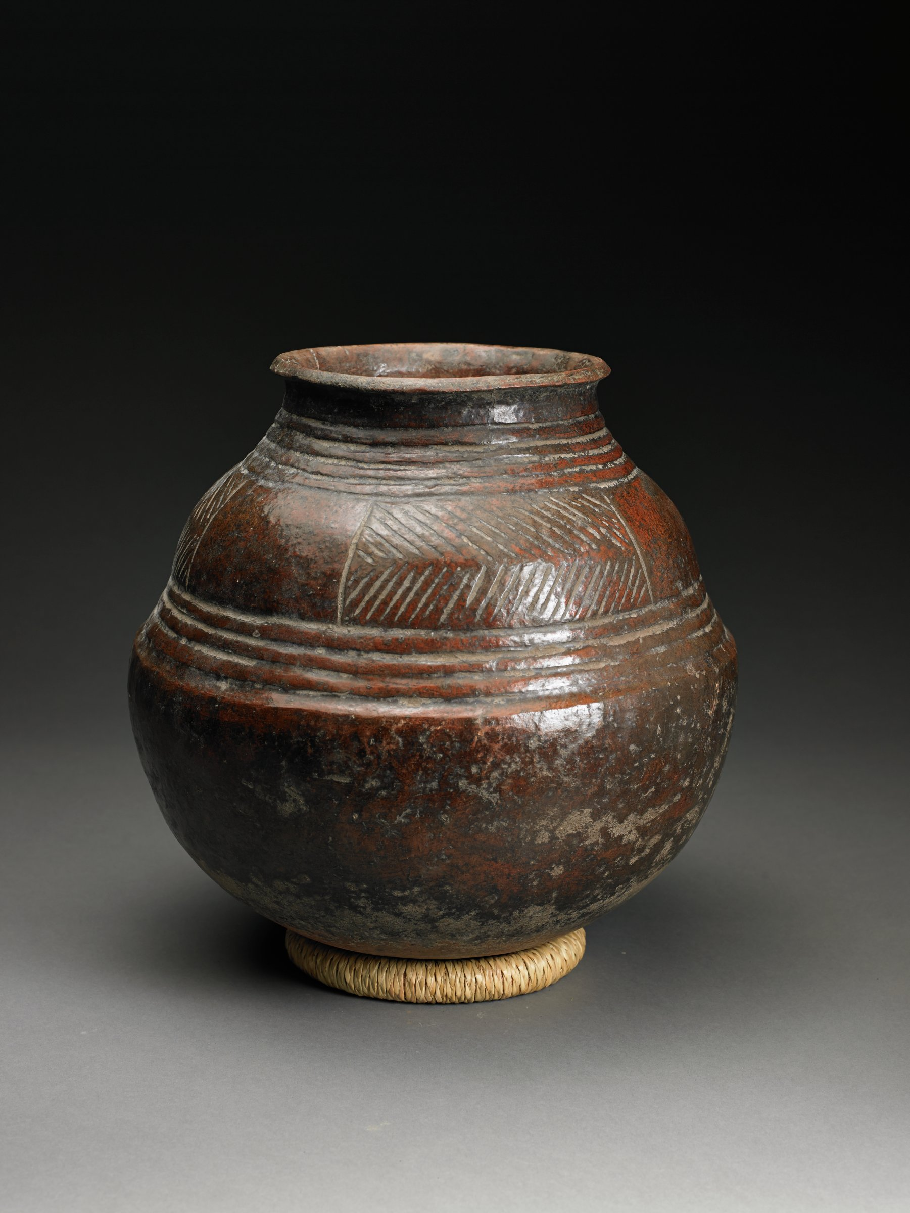 Dark brown glossy vessel has rounded bottom which is larger than top half of vessel; mid-point marked by raised bands.  Shoulder has herringbone pattern.