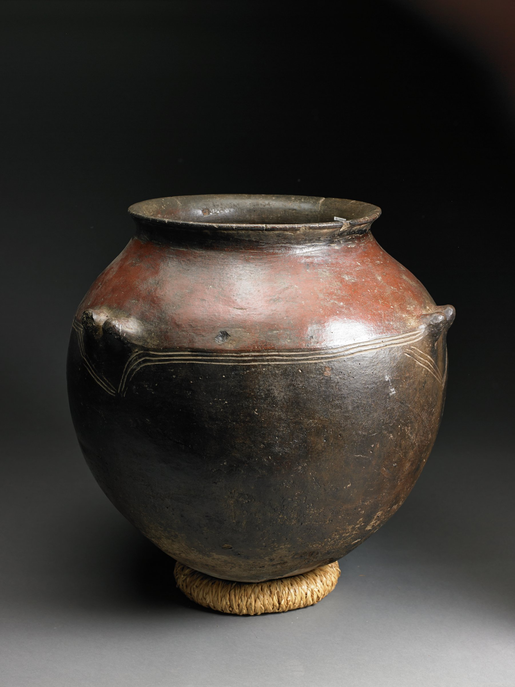Round, dark brown vessel with glossy surface has short, curved rim. Three parallel incised lines mark shoulder, which has four pairs of upturned knob handles.