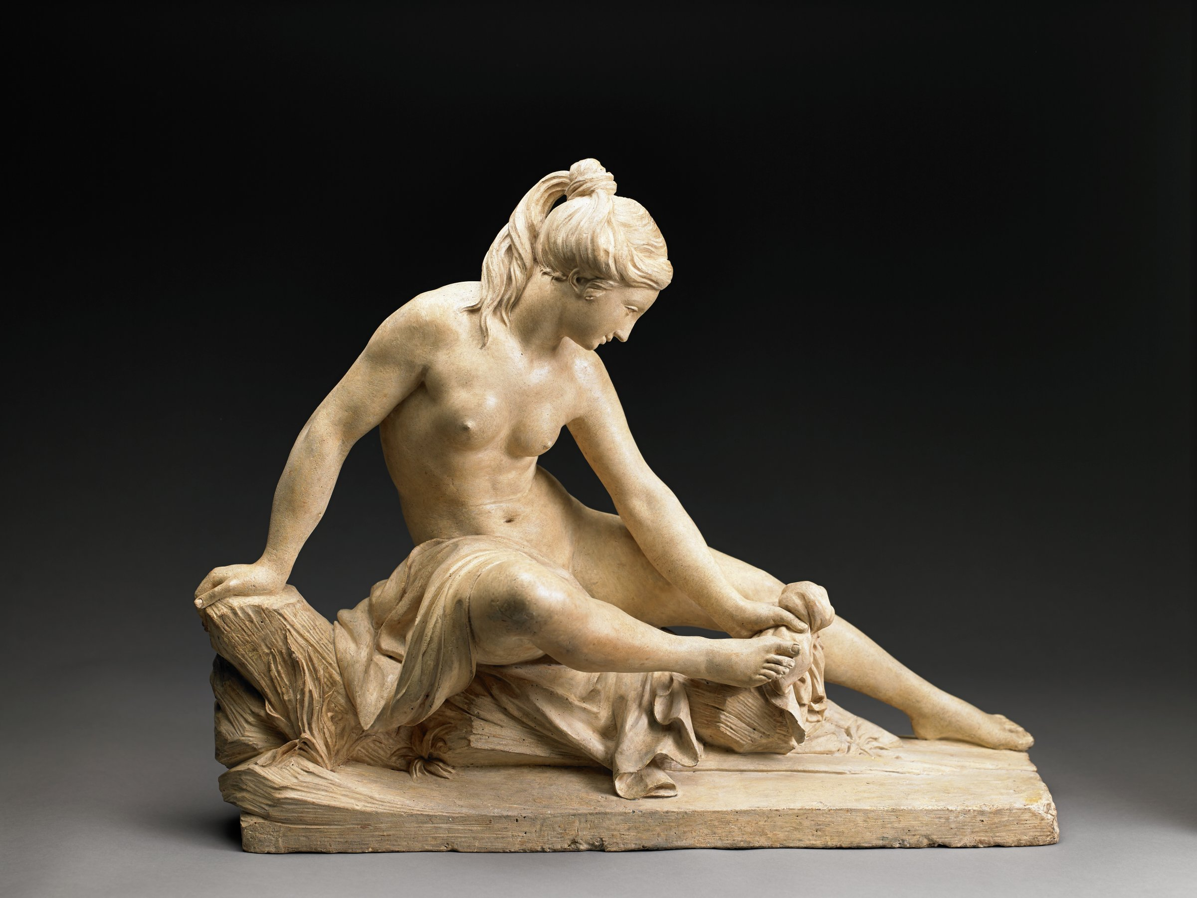 A woman sits leaning on her right arm as she baths with her left hand. Her gaze is cast downwards as she focuses on her movements. Her right leg is bent and slightly lifted. Her hair is pulled up on the crown of her head.
