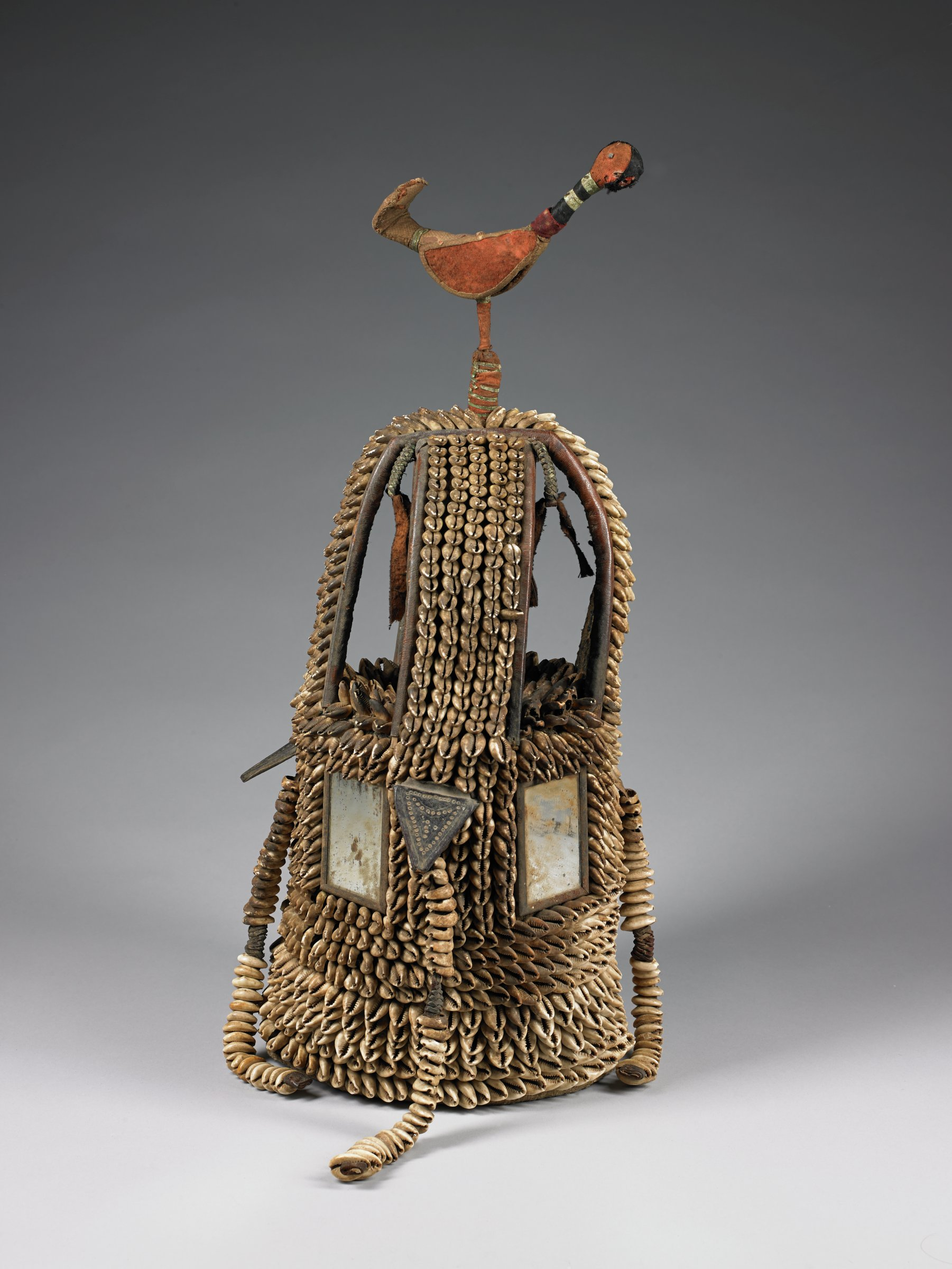 Cowrie shell covered shrine with stone axe head, surmounted with bird finial