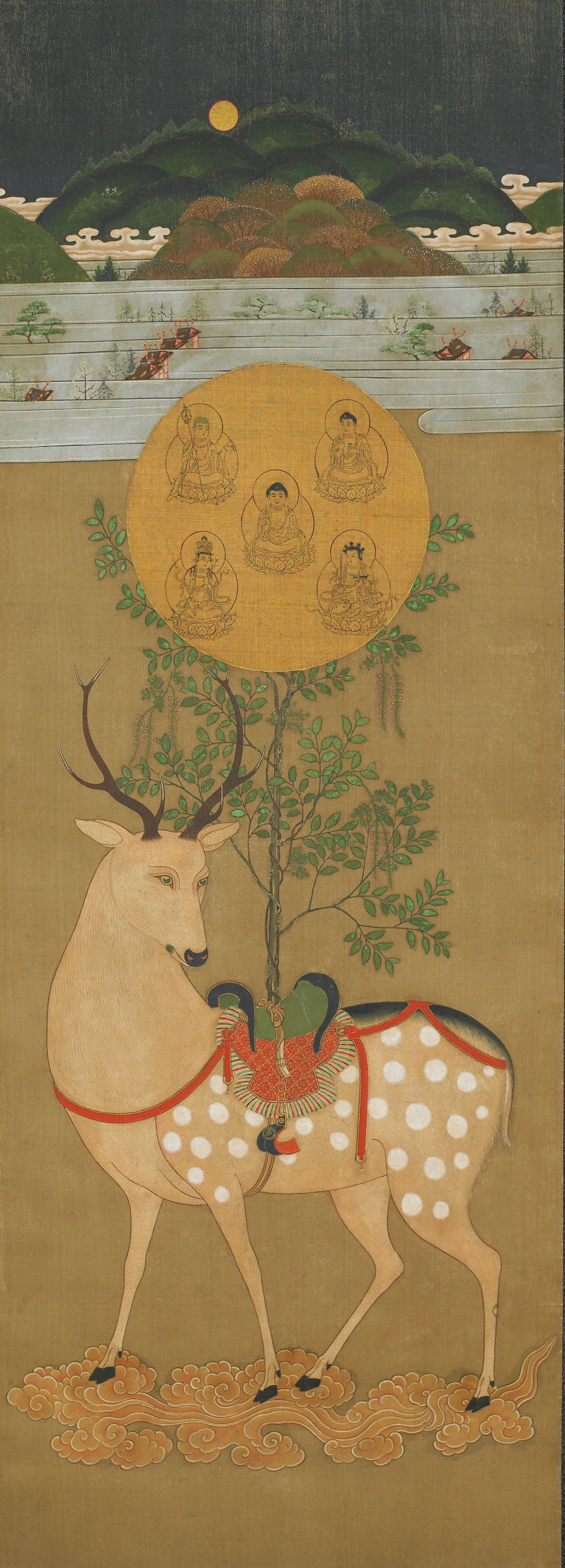 A hanging scroll depicting a deer standing with a mirror on the saddle on its back. The mirror holds the images of five Buddhist deities. In the background is the Kasuga shrine in Nara. The deer is the symbol of the Shinto gods who live there.