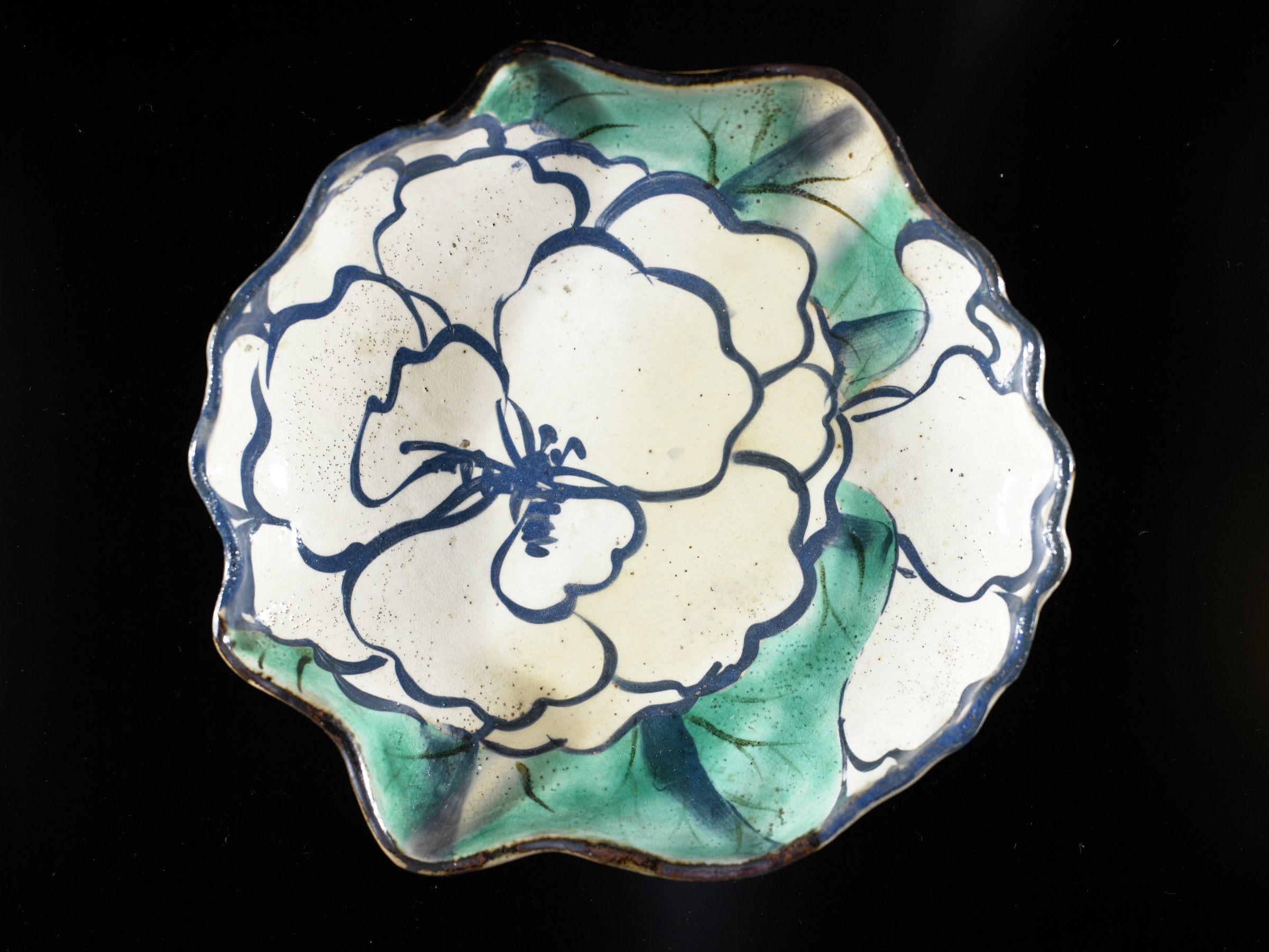 Dish in irregular peony form decorated inside with two white peonies in linework on green enamel background; unglazed bottom; painted grass blades on exterior.