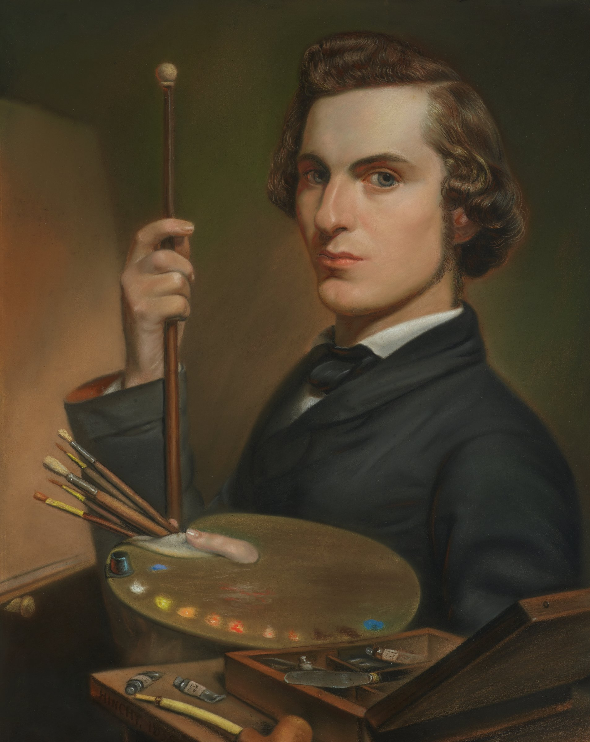This a bust-length portrait of a man with long sideburns, wavy brown hair and gray eyes, who gazes directly at the viewer. In his right hand, he holds a mahlstick; in his left hand, he holds a painter's palette, loaded with oil paint, and five brushes. In the foreground, a smoking pipe, two tubes of oil paint, and an open artist's box (containing several tubes of paint and a palette knife) rest on a table. In the background to the left, a blank canvas rests on an easel (only the bottom left rung of the easel is visible).