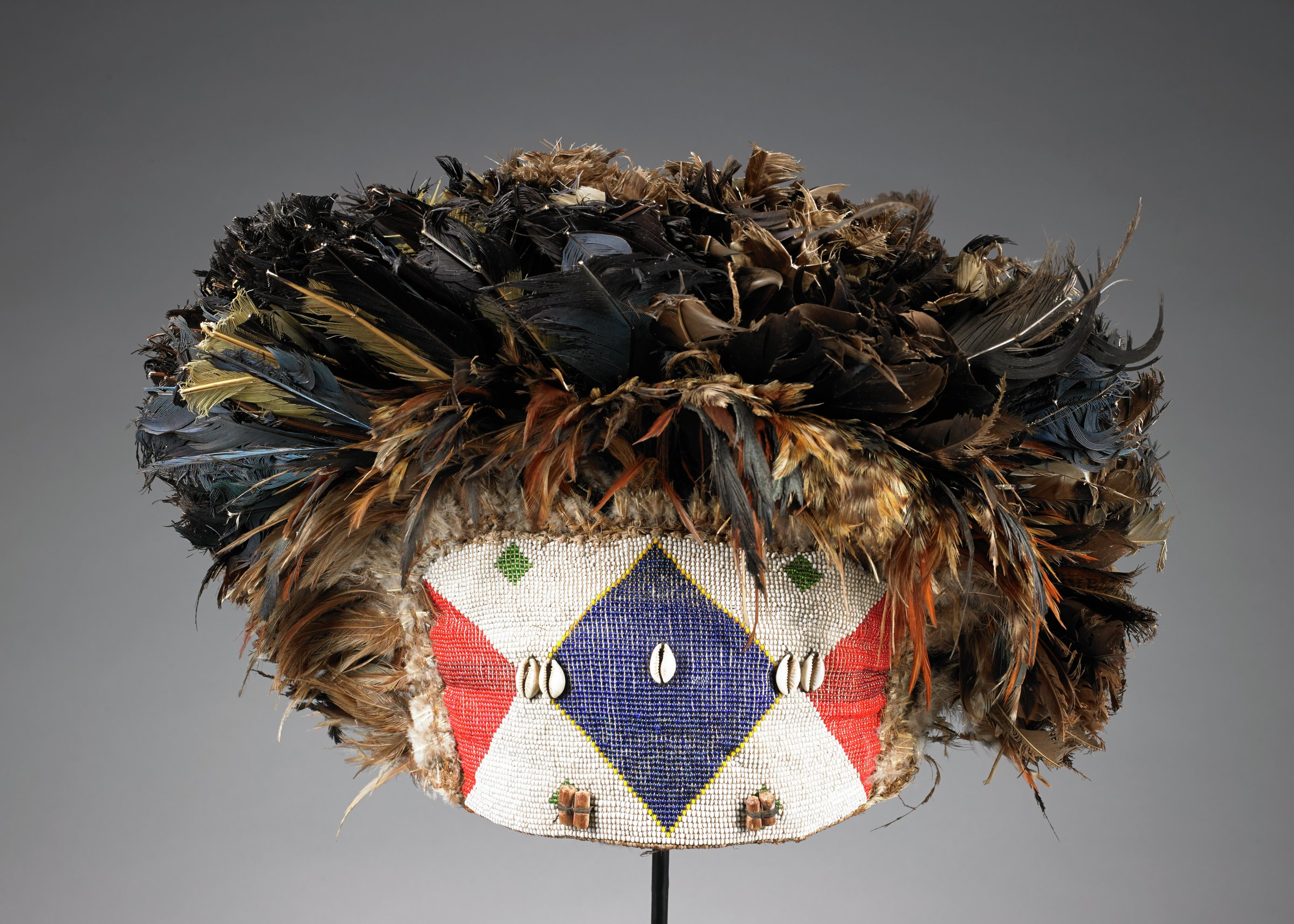 Headdress of burlap and animal hide, front beaded with red, blue, white, and green glass beads in lozenge and triangle patterns. Five cowrie shells and four wooden peg beads attached on top of surface of glass beads. Wooden pegs, joined in pairs, cover small lozenges of green glass beads. White, brown, black, and blue feathers cover top, sides and back of headdress in spherical shape (slightly flattened in back). Five short wooden dowels attached to back, arranged two, one, two.