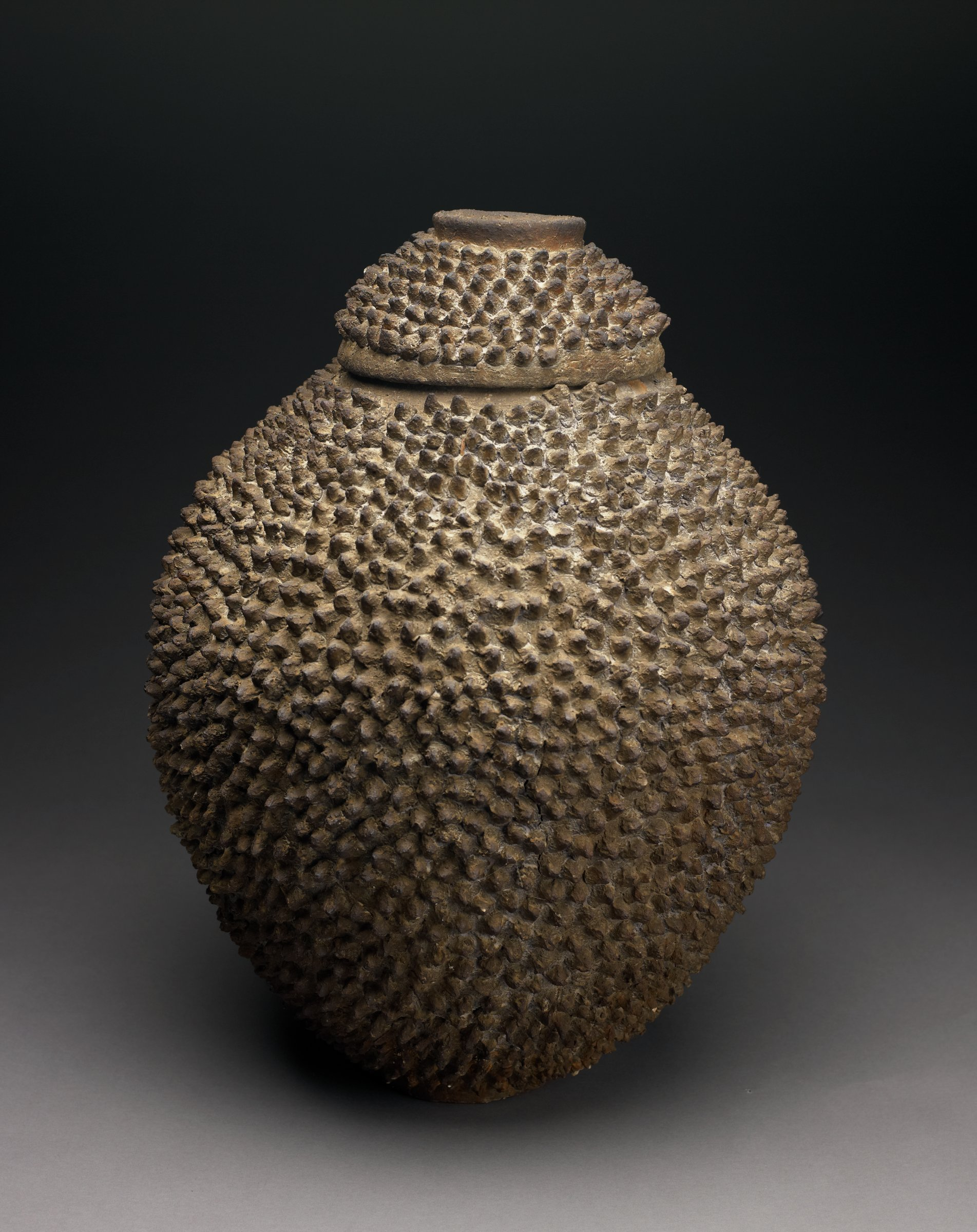 """Jar with cover, both covered entirely with clay """"spikes."""""""