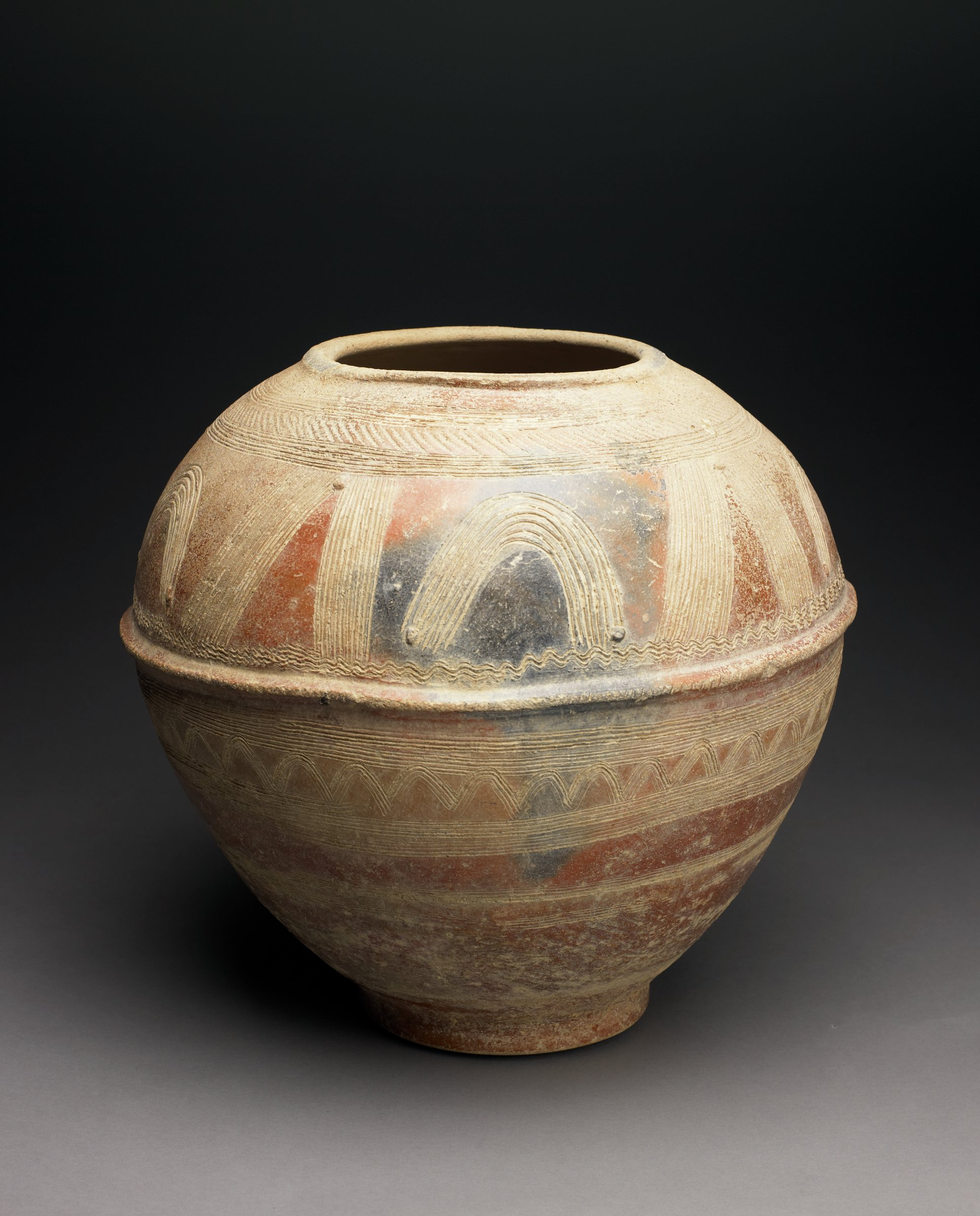 Large round jar with foot, narrows slightly toward the bottom. Raised ridge around widest portion of vessel. Shoulder decorated with groups of angled and curved parallel incised lines; bottom half with incised geometric patterns. Reddish color with fire clouds.