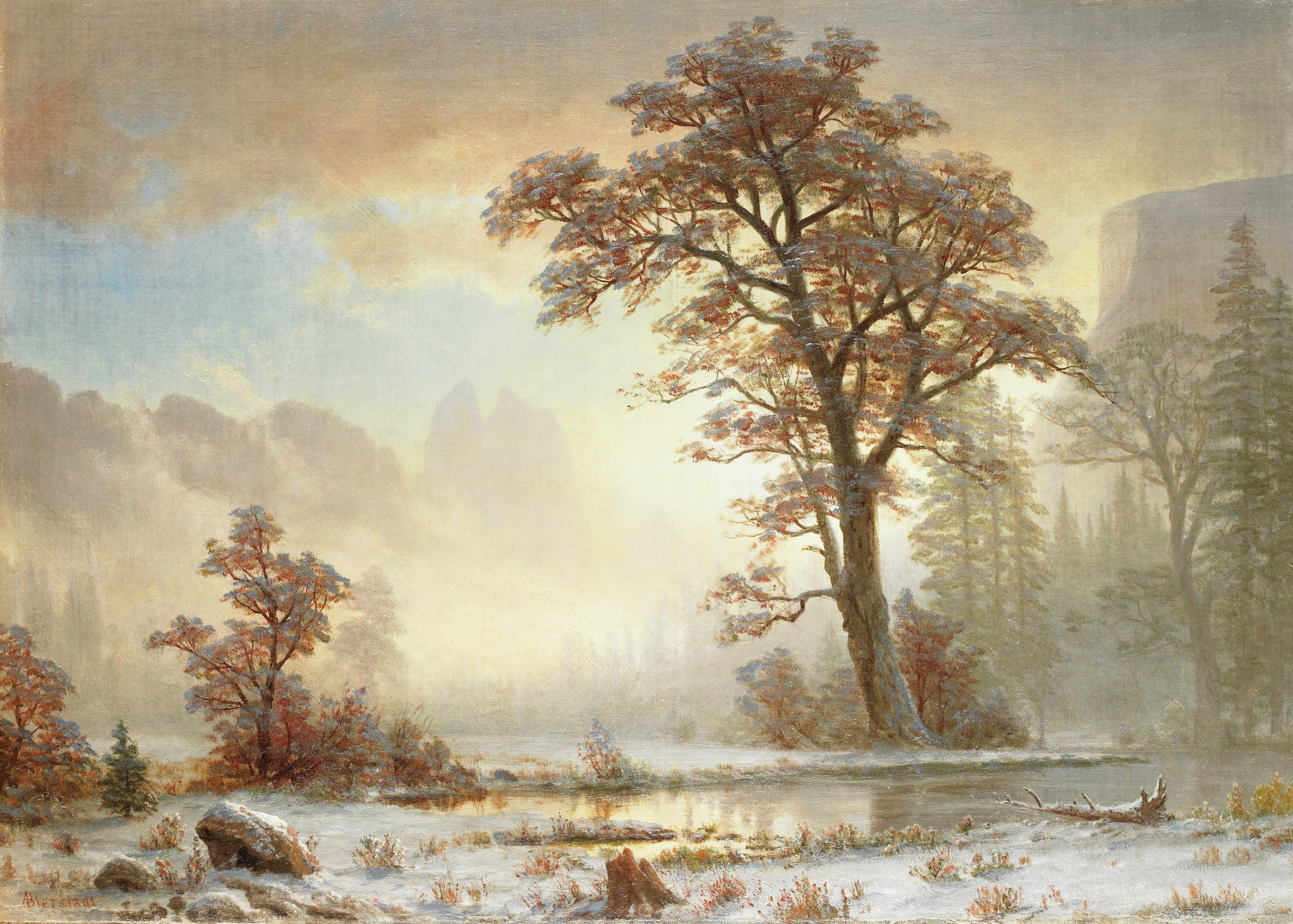In this painting, a valley flanked by rocky mountains on two sides (Yosemite Valley) is blanketed with a thin layer of snow. In the center of the canvas, a large tree with orange leaves extends vertically through the composition, standing just behind a body a shallow, still river. The middle ground is composed of trees—both pines and leafy trees with autumnally colored foliage—masked by a hazy atmosphere.