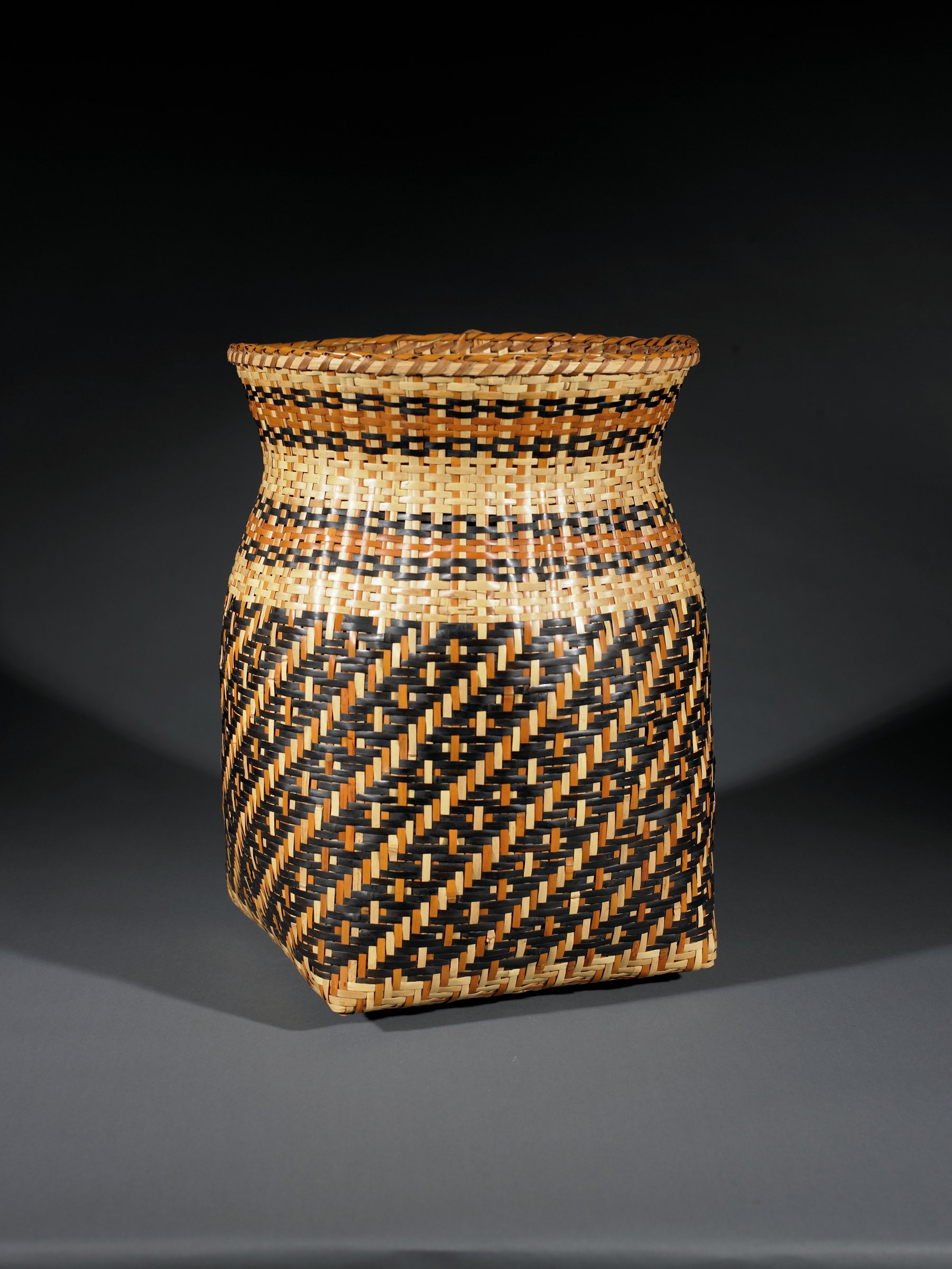 Single-weave river cane storage basket with square bottom and round body, neck, and mouth. Body of basket has dark diagonal bands; neck and shoulder of basket have bands of dark brown and red.